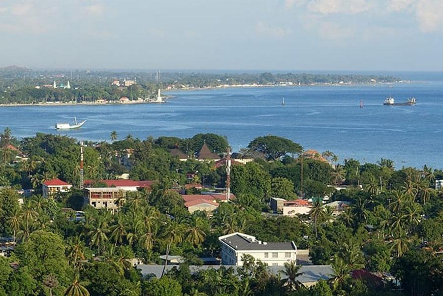 Timor-Leste: Nature, Land, Outdoors, Shoreline, Water, Sea, Ocean, Neighborhood, Building, Urban, Plant, Vegetation, Landscape, Scenery, Suburb, Coast, Tree, Aerial View, Vehicle, Boat, Transportation, Panoramic, Woodland, Forest, Grove, Promontory