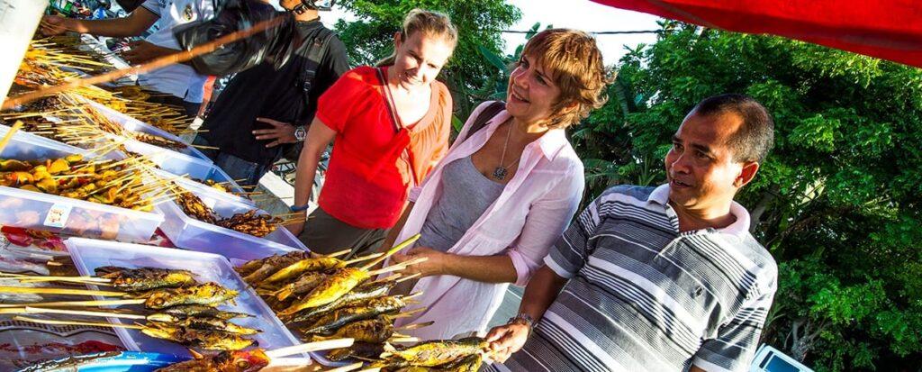 Timor-Leste: Human, People, Person, Bbq, Food, Conifer, Flora, Plant, Tree, Yew, Clothing, Shirt, Market, Seafood, Bakery, Shop, Forest, Land, Nature, Outdoors, Rainforest, Vegetation, Jar, Potted Plant, Pottery, Vase, Corn, Grain, Produce, Vegetable, Grocery Store, Jungle, Face, Portrait